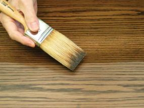 applying wood finish with a brush